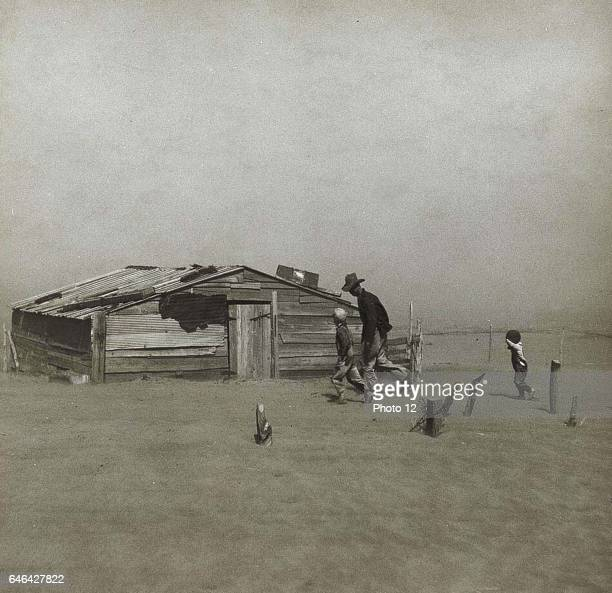 Storm in the Dust Bowl United States Man and boys walking towards wooden hut gradually being covered by windblown dust Small boy is holding up his...