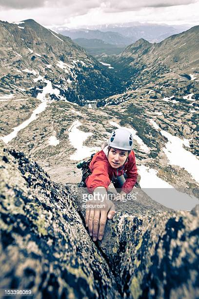 Storm looming behind a female rock climber in Colorado