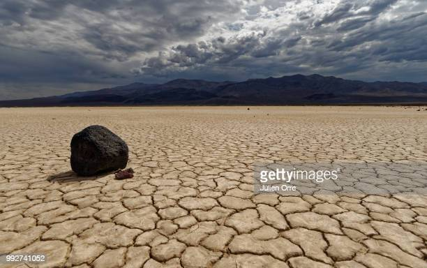 a storm moving over a dry, cracked landscape. - environmental damage stock pictures, royalty-free photos & images