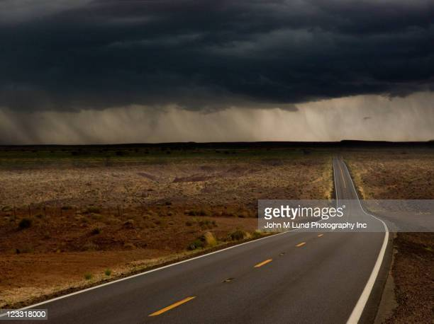 storm over remote highway - ominous stock photos and pictures