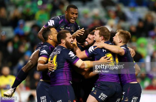 Storm players celebrate a try by Dale Finucane during the round 20 NRL match between the Canberra Raiders and the Melbourne Storm at GIO Stadium on...