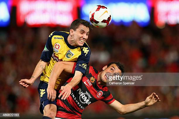 Storm Roux of the Mariners heads the ball over Mark Bridge of the Wanderers during the ALeague Semi Final match between the Western Sydney Wanderers...