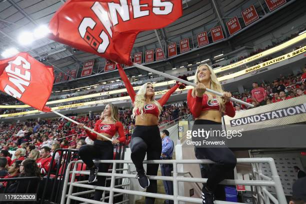Storm Squad members of the Carolina Hurricanes wave flags and cheer during a time out of an NHL game against the Montreal Canadiens on October 3 2019...