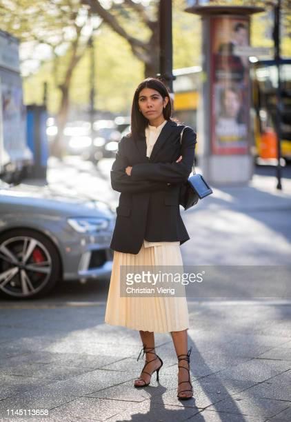 Storm Westphal is seen wearing beige pleated skirt top black blazer bag heels on April 25 2019 in Berlin Germany