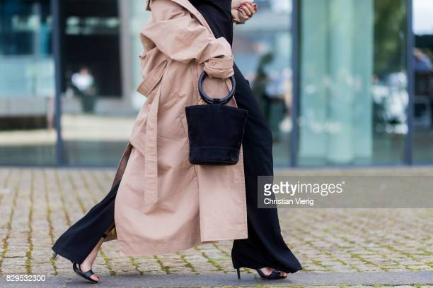 Storm Westphal wearing bucket bag black pants black top trench coat outside Designers Remix on August 10 2017 in Copenhagen Denmark