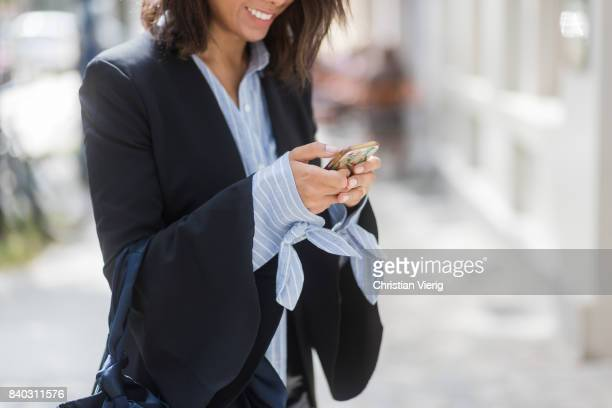 Storm Westphal writting a text message with her phone wearing a black Iris und Ink blazer a blue white striped Edited blouse black other Stories mini...
