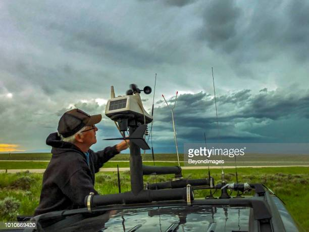 storm-chaser adjusts the rooftop weather station on his chase vehicle as a severe storm builds in the background - extreme weather stock photos and pictures