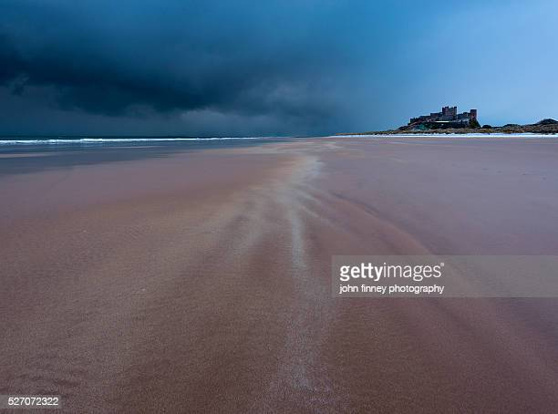 Stormy Bamburgh Castle seen from the beach in Winter. Northumberland. UK. Europe.