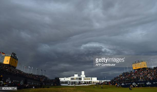 Stormy clouds gather over the 18th hole and the ArtDecostyle clubhouse as play comes to a close on day three of the Open Golf Championship at Royal...