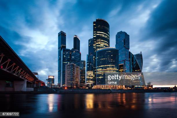 stormy clouds over skyscrapers business buildings in the night - moscow international business center stock photos and pictures