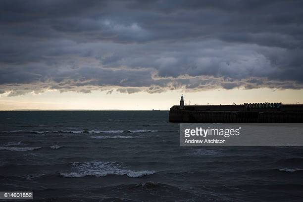 A stormy day with dark clouds looms over the lighthouse on Folkestone Harbour Arm with France in the distance 6th October 2016 Folkestone Kent United...