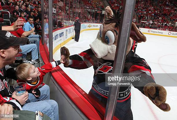 Stormy mascot of the Carolina Hurricanes interacts with a young fan during a NHL game against the Ottawa Senators on October 25 2011 at RBC Center in...