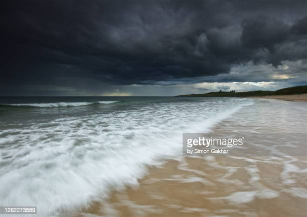 stormy seascape photograph on beach with water motion - north sea stock pictures, royalty-free photos & images