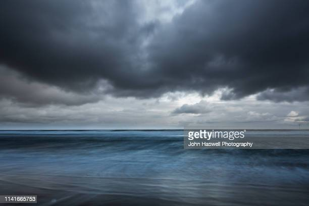 stormy sky northumberland - dramatic sky stock pictures, royalty-free photos & images