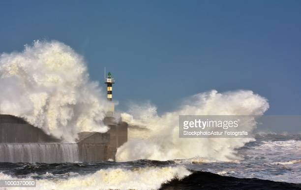 Stormy wave over lighthouse of San Esteban de Pravia.