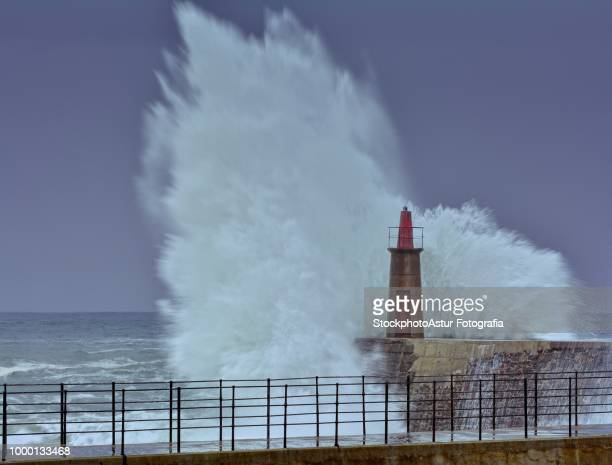 Stormy wave over old lighthouse and pier of Viavelez.
