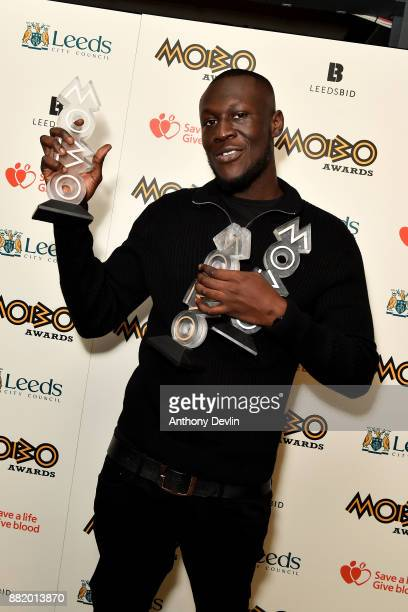Stormzy poses in the winners room with the awards for Best Male Best Grime and Best Album at the MOBO Awards at First Direct Arena Leeds on November...