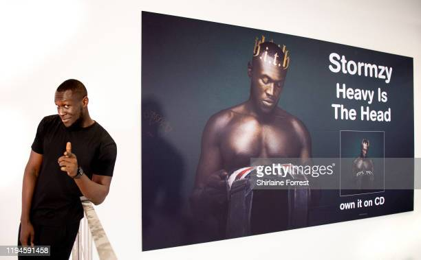 Stormzy poses with his enormous poster after meeting fans and signing copies of his new album 'Heavy Is The Head' during an instore session at HMV...