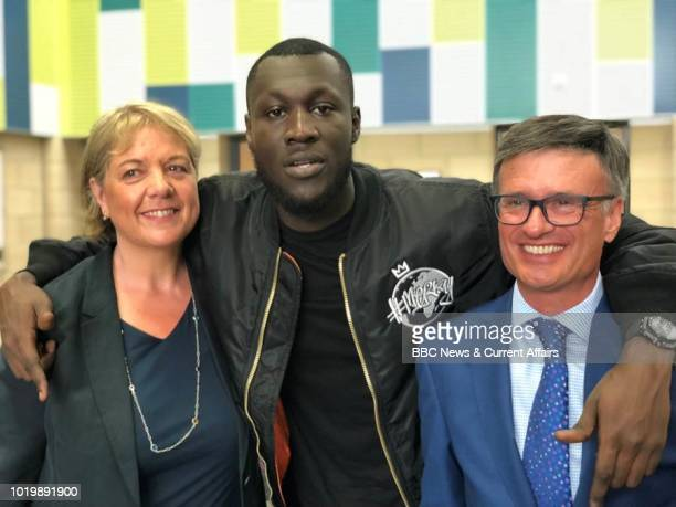 Stormzy poses with poses with CEO of Harris Federation Sir Dan Moynihan and a former teacher as he visits his old school Harris City Academy in south...