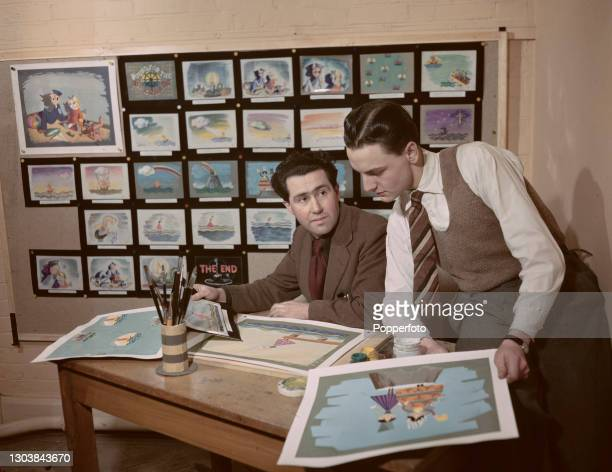 Story, sketch and background artist Waclaw 'Wacky' Machan shows English entertainer, comedian and artist Bob Monkhouse some of the brightly coloured...