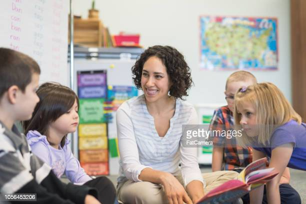story time in an elementary classroom - montessori education stock pictures, royalty-free photos & images