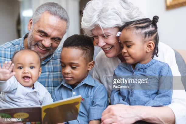 story time with grandma and grandpa - mixed race person stock pictures, royalty-free photos & images