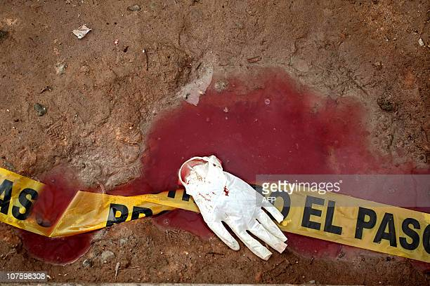 STORYBlood and a surgical glove are seen on the floor of a house where at least 11 youngsters were killed and 17 others were injured during a party...