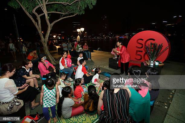 A storyteller tells a story about the Singapore popular folklore at Boat Quay during the Singapore River Festival on October 24 2015 in Singapore
