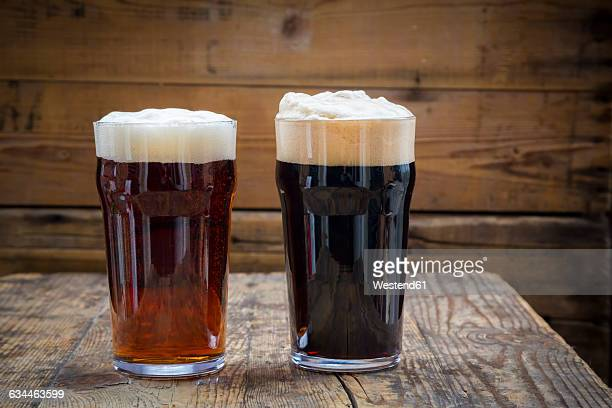 stout and red ale in pint glasses - british culture stock pictures, royalty-free photos & images