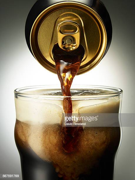 Stout beer pouring from a can into a glass