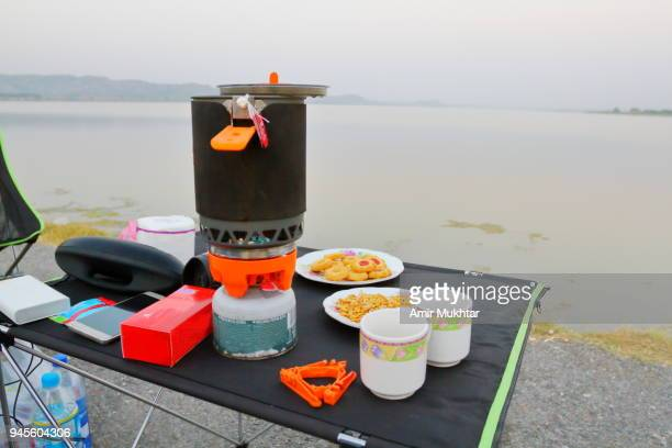 stove and tea utensils on lake - amir mukhtar stock photos and pictures