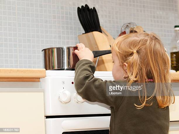Stove danger in kitchen for a small child with blond hair
