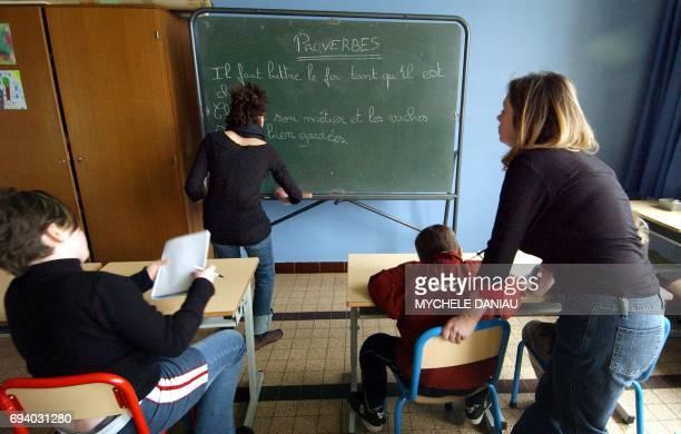 Stéphanie référente à l'accompagnement scolaire surveille et aide à faire leurs devoirs le 01 mars 2005 un groupe d'enfants après les heures de...
