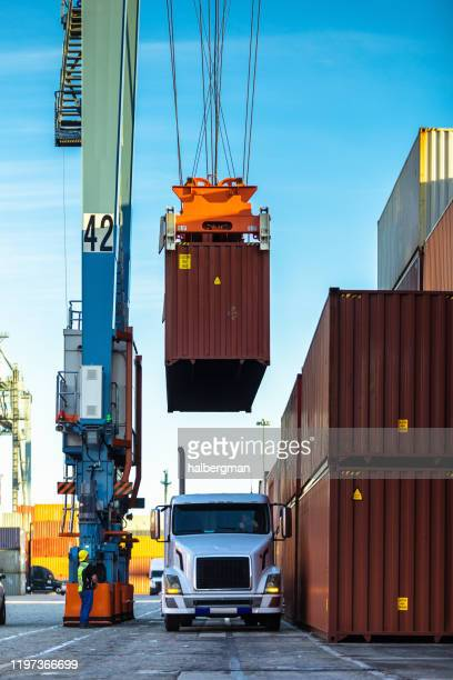 straddle carrier lifting cargo container from truck - port of los angeles stock pictures, royalty-free photos & images