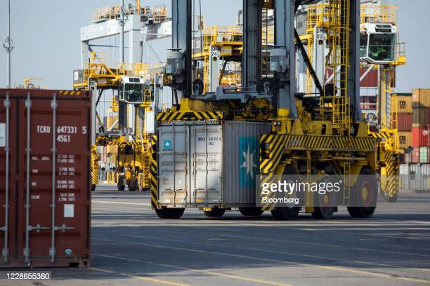 A straddle carrier moves a shipping container owned by AP MollerMaersk A/S away from the quayside at London Gateway port operated by DP World Plc in...