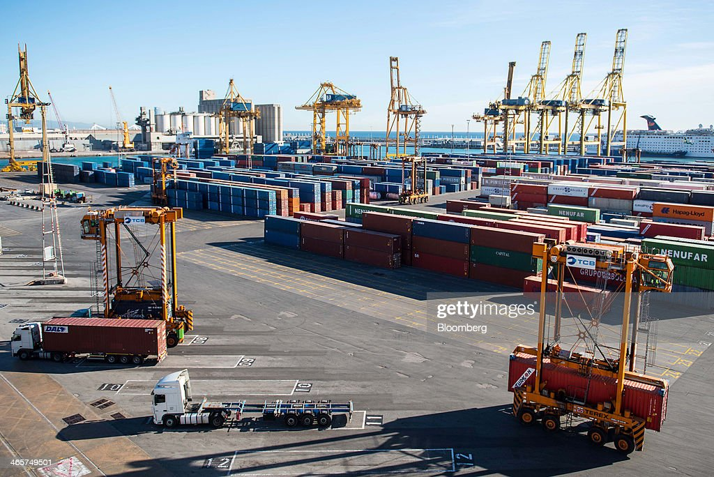 Straddle carriers move shipping containers around the quayside at the commercial port in Barcelona, Spain, on Wednesday, Jan. 29, 2014. Government bonds in Europe's most-indebted countries rallied in the first three weeks of the year on signs the debt crisis that pushed those nations' borrowing costs to euro-era records had abated. Photographer: David Ramos/Bloomberg via Getty Images
