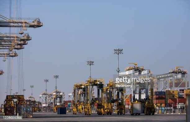 Straddle carriers move shipping containers on the quayside at London Gateway port operated by DP World Plc in StanfordleHope UK on Tuesday Sept 22...