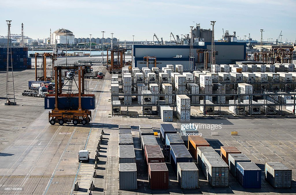 Straddle carriers operate among shipping containers stored on the quayside at the commercial port in Barcelona, Spain, on Wednesday, Jan. 29, 2014. Government bonds in Europe's most-indebted countries rallied in the first three weeks of the year on signs the debt crisis that pushed those nations' borrowing costs to euro-era records had abated. Photographer: David Ramos/Bloomberg via Getty Images