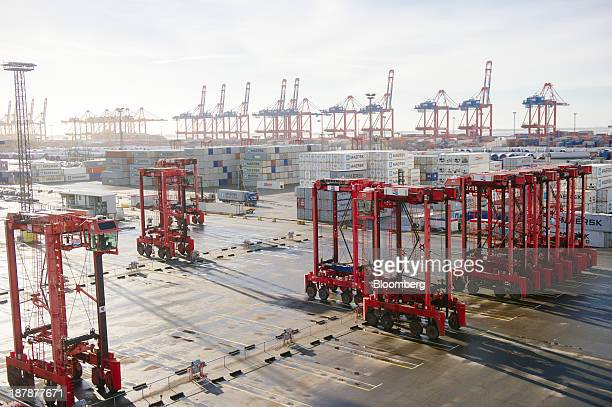 Straddle carriers stand on the dockside beside the Maersk McKinney Moeller TripleE Class container ship operated by AP MoellerMaersk A/S in the Port...