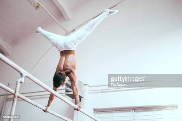straddle handstand - parallel bars gymnastics equipment stock photos and pictures