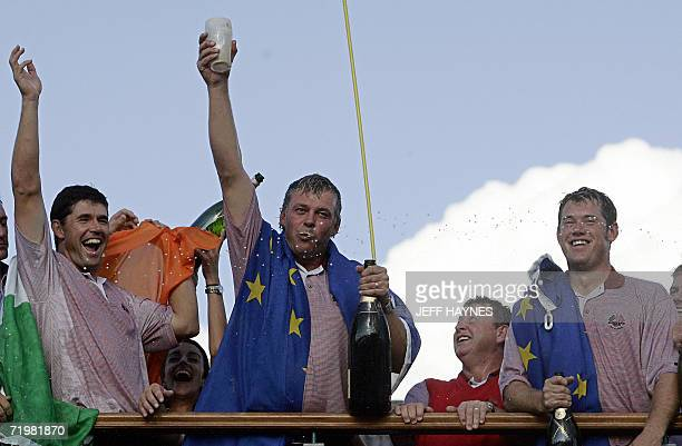 European Ryder Cup player Darren Clarke celebrates drinking a pint of Guiness beer in one as teammates Padraig Harrington and Lee Westwood look on as...