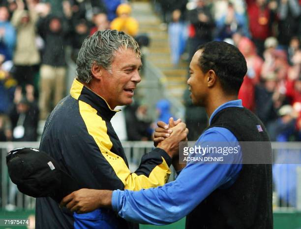 European Ryder Cup player Darren Clarke is congratulated by United States player Tiger Woods on the 16th hole after Clarke and Westwood beat Woods...