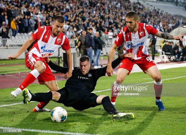 Strahinja Pavlovic of Partizan is challenged by Dusan Jovancic and Aleksa Vukanovic of Crvena Zvezda during the Serbian Cup Semi Final match between...