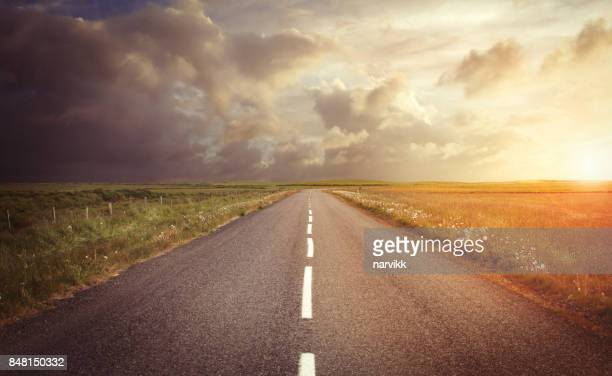 straight empty road in sunset light - dramatic sky stock pictures, royalty-free photos & images