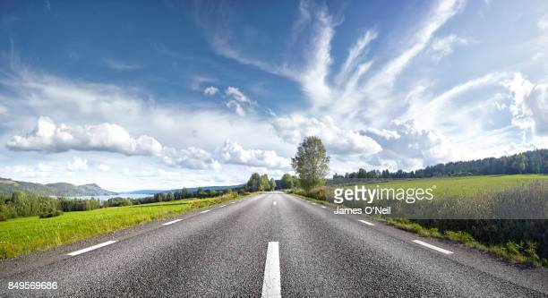 straight empty road, sweden - strada foto e immagini stock