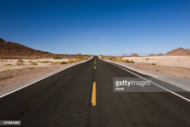 Straight, empty, two-lane road in the middle of the desert