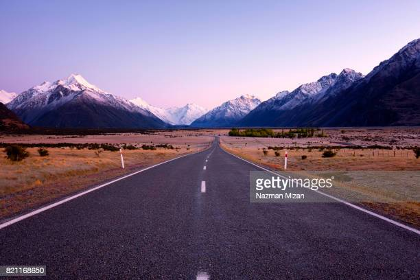 a straight highway leading to the snow capped mountains. - porträt bildbanksfoton och bilder