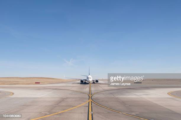 straight on view of a jet airplane taxing on an airport runway - airport runway stock pictures, royalty-free photos & images
