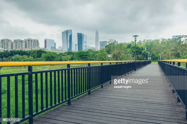straight park footbridge under overcast sky - guangdong province stock photos and pictures