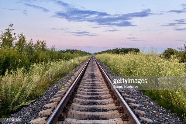 straight railway line in twilight - railroad track stock pictures, royalty-free photos & images
